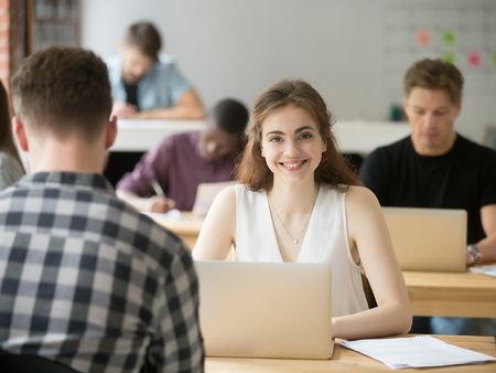 Smiling woman looking at camera sitting at desk in co-working